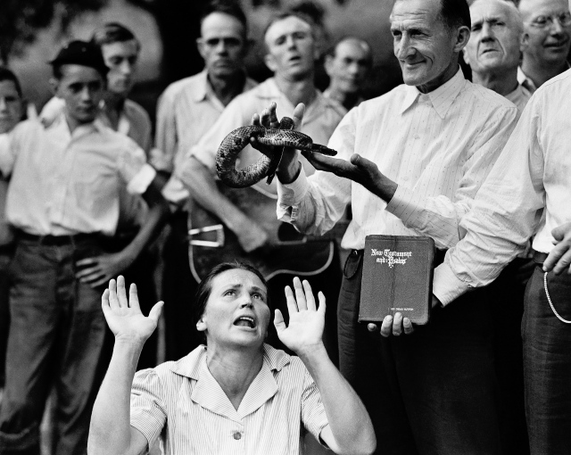 "FILE - In this Aug. 22, 1944 file photo, members of the Pentecostal Church of God, a faith healing sect, surround a woman who has ""Got the Spirit"" as a man holds a snake above her head in Evarts, Ky. Although a Kentucky statute passed in 1940 prohibits the handling of snakes in connection with religious services, this sect revived the ritual after the recent death of a native of the region who was bitten by rattlesnake. (AP Photo)"